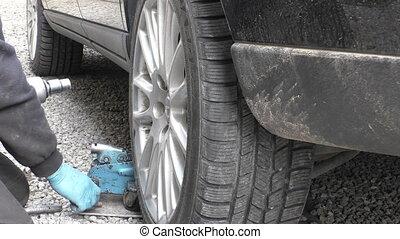 Removing car wheel on roadside - Mechanic unscrewing bolts...