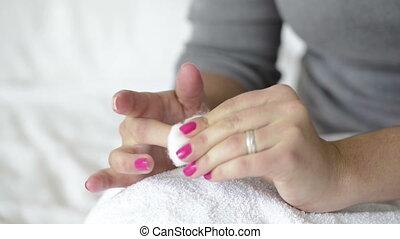 Removing Nail Polish - Woman with painted nails uses nail...