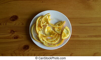 Removing orange peel from a plate on a wooden table.