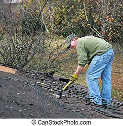 removing shingles - construction worker removes shingles...
