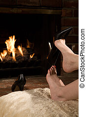 Removing shoes by fire - Woman\\\'s legs removing high heel...