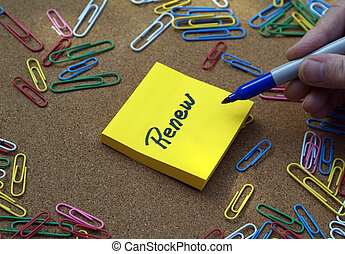 """""""Renew"""" written on a yellow post it note, with hand holding pen and bulletin and colorful paperclips behind."""
