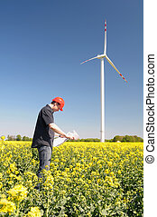 Renewable energy constructor standing on yellow field of rape behind blue sky with windmill.