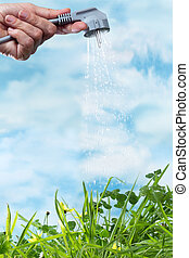 Electrical plug watering a green grass meadow as a symbol of green and renewable energy