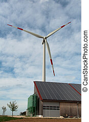 Renewable Energy - barn covered with solar panels and wind...