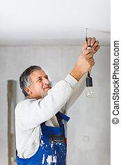 renovado, appartment, instalación, recientemente, bombilla, hombre mayor