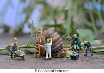 Renovate your home. Snail and workers figurines