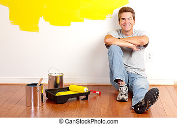 Renovation - Smiling handsome man painting interior wall of...