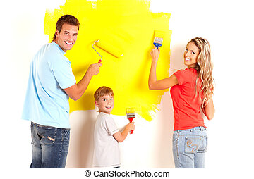 Renovation. Young family painting interior wall of home.