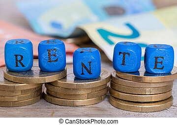 Rente (in german pension) letter cubes on coins concept.