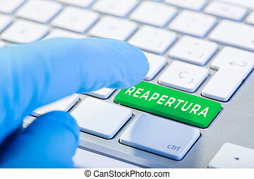 Reopening word in spanish language on green key Keyboard. Coronavirus Covid-19 pandemic. Hand with protective glove ready to push the button