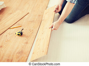 close up of male hands intalling wood flooring