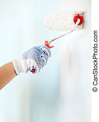 close up of male in gloves painting wall - repair, building...