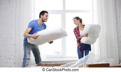 smiling couple opening big cardboard box with sofa