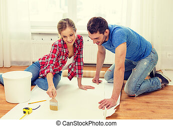 smiling couple smearing wallpaper with glue - repair, ...