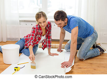smiling couple smearing wallpaper with glue - repair,...