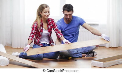 repair, building and home concept - smiling couple taking out wood flooring from package