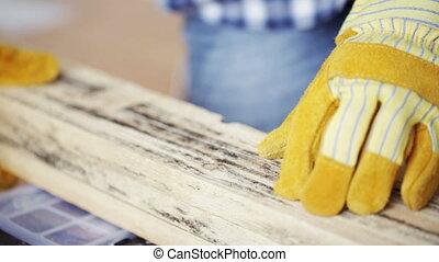 close up of man hammering nail to wooden board - repair, ...