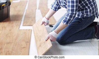 close up of man installing wood flooring - repair, building,...
