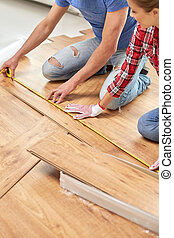 happy couple with ruler measuring parquet board