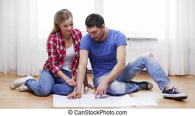 smiling couple discussin blueprint at home