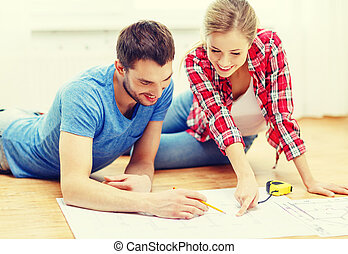 smiling couple looking at blueprint at home - repair,...