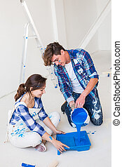 Repair, color, people concept - couple going to paint the wall, they are preparing the color