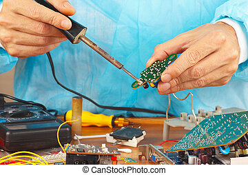 Repair electronic board of device with a soldering iron in...