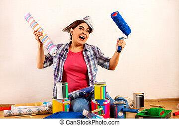 Repair home senior woman holding paint roller for wallpaper.
