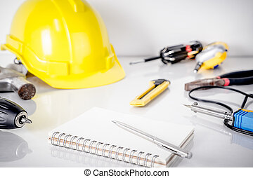 Repair man, construction worker tools with planner book on table