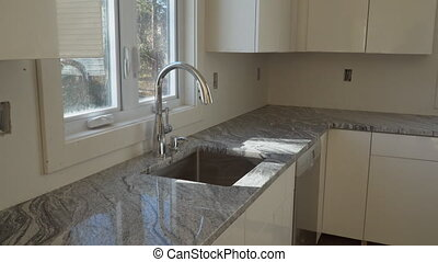 Repair man In Overalls Repairing Cabinet Hinge In Kitchen Installation of kitchen. Worker installs doors to kitchen cabinet.