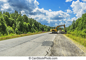 PERM KRAI, RUSSIA - JULY 12, 2016: The repair of the road using an excavator on a summer day