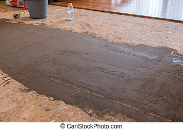 Flooring cement to level the subfloor in room before laying new hardwood flooring