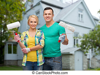 smiling couple with paint rollers over house - repair, ...