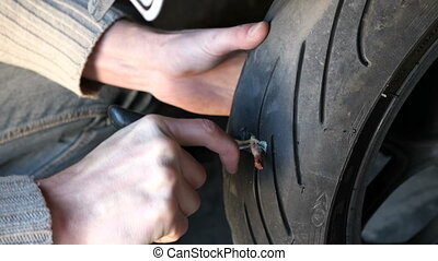Repair puncture tubeless tires motorcycle with a harness, do it yourself.