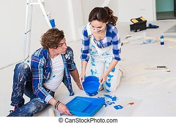 Repair, renovation and people concept - couple going to paint the wall, they are preparing the color