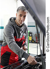 Repair the car, a man at work - Car mechanic working in a...