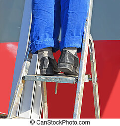 Repair. The worker's feet in a uniform on a step-ladder.