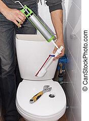 repair toilet cistern - plumber repairing the drain valve in...