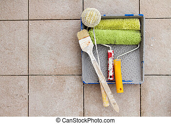 Repair tools over stone floor tile background. Copy space.