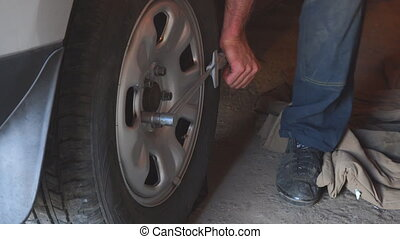 Repair wheels in the garage. Man replaces the wheel