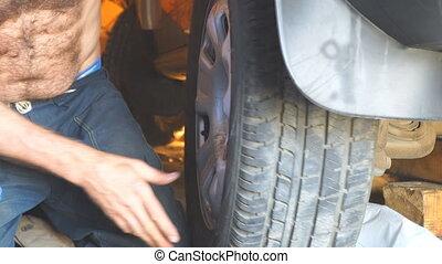 Repair wheels in the garage. Man replaces the wheel
