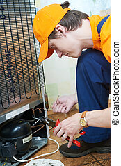 repair work on fridge appliance - Repairman makes...