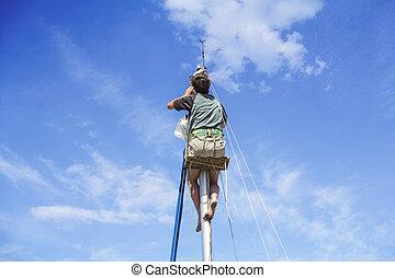 Repair yacht mast - Young man hanging and repairs yacht mast