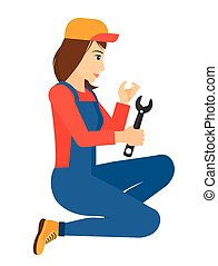Repairer holding spanner. - Young repairer sitting with a...