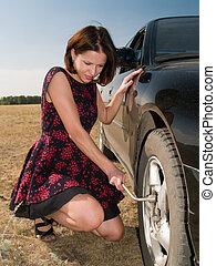 Repairing - A beautiful young woman repairing a car, unscrew...