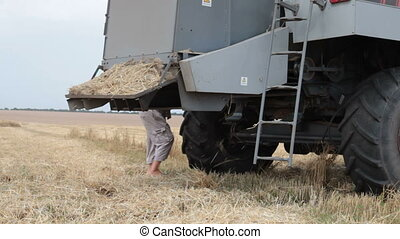 repairing combine harvester in a wheat field