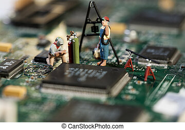 Repairing Electronic Circuitry. A miniature model figurine of a welder at work on a circuit board, macro.