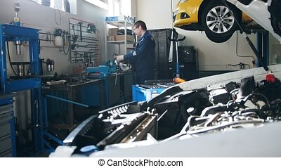 Repairing of cars - worker grinding metal construction with a circular saw, small business