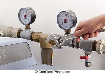 Repairing water softener - Man's hand with wrench repairing ...